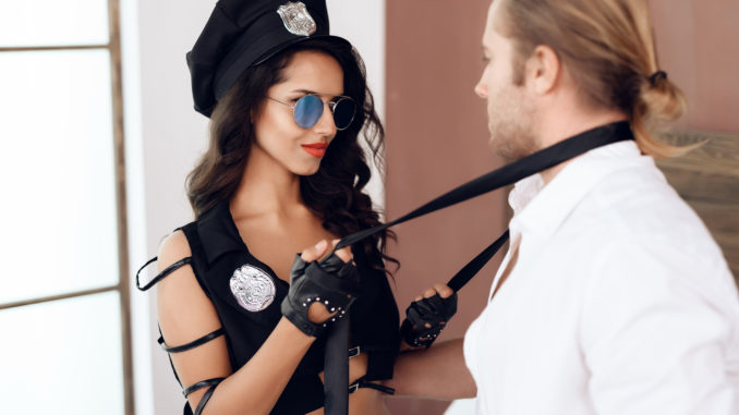 Passionate young women in police uniform takes off with tie from long haired men in bedroom.