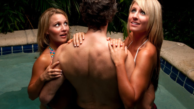 caucasian girls flirting with young man in a jacuzzi.