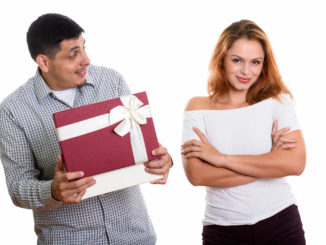 men looking at women while opening gift box looking surprised