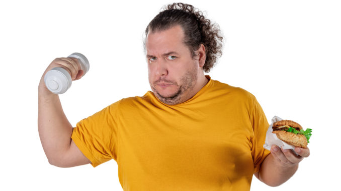 Funny fat man eating unhealthy food and trying to take exercise isolated