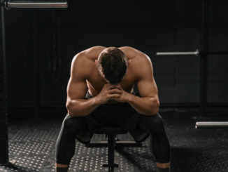 Strong sporty man sitting on gym bench suffering breakdown to overcome.