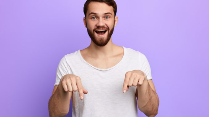 Handsome positive bearded man pointing down with two fingers.