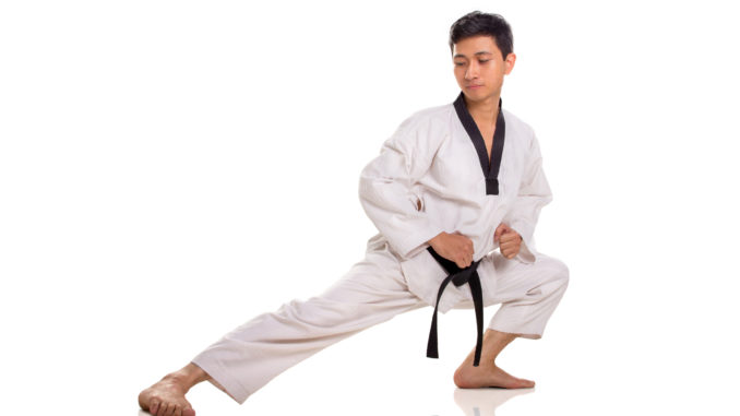 Full length portrait of a male traditional martial art practitioner stretching his right leg