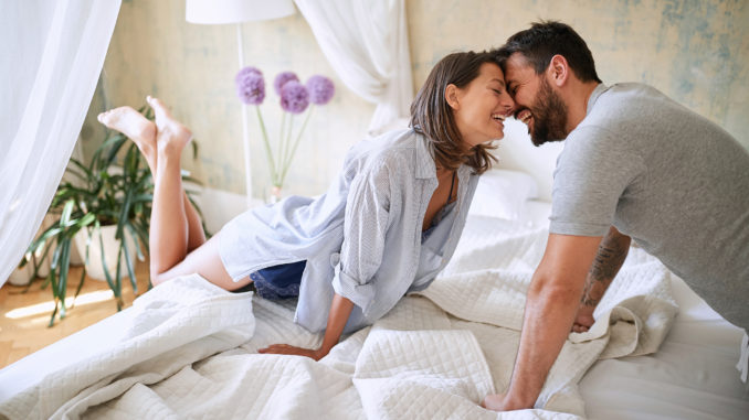 Couple cuddling in the morning while making the bed