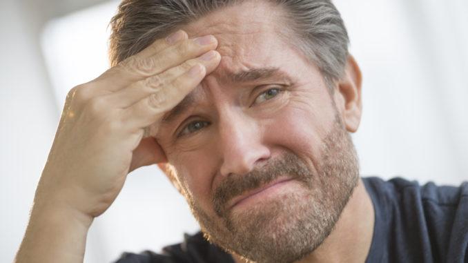 Closeup of mature man with headache rubbing forehead