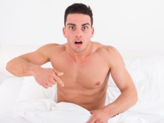 Surprised and shocked half naked young man in bed looking down at his underwear