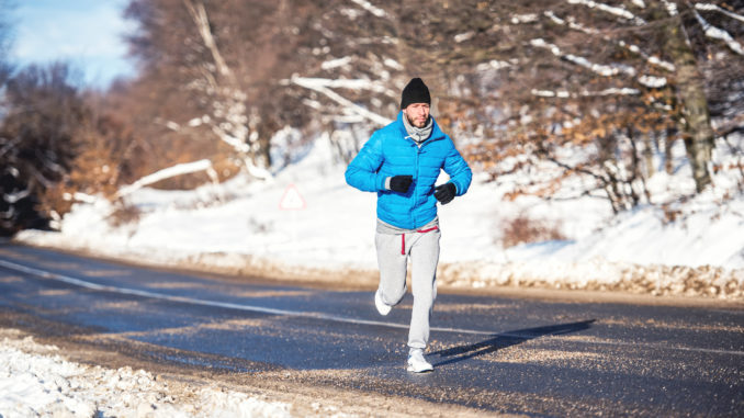 Active man, jogging and running during a sunny winter day. Outdoor working out concept