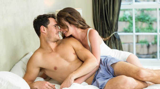 Young couple cuddling on bed in bedroom