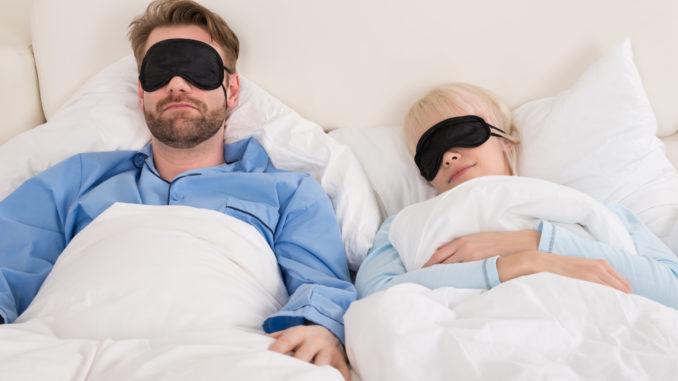 Young Couple Sleeping Comfortably On Bed Using Eye Mask