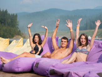 Man is surrounded by two women sitting on a cushioned lounger with his hands raised up