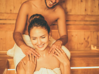 Young happy couple relaxing inside a sauna at spa resort hotel luxury - Romantic lovers having a bodycare day in steam bath man making a massage for his girlfriend - Relax, love, lifestyle concept