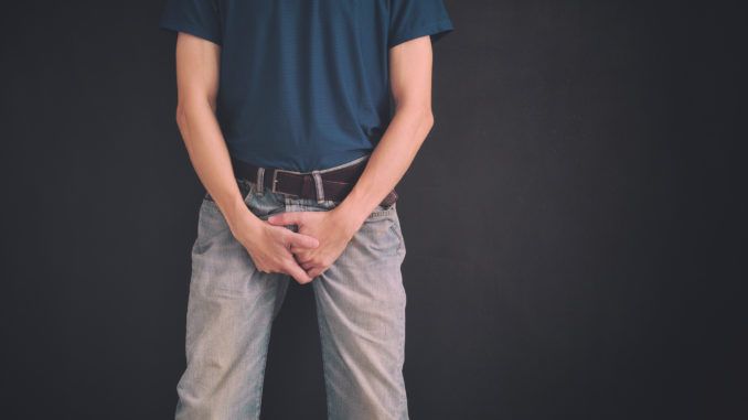 Man in jeans covers his crotch with hands against black wall.
