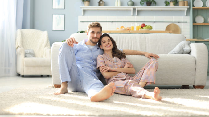 The happy couple in pajamas sitting on the floor background of the sofa in the living room.