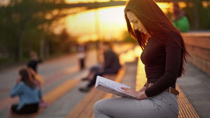 Young Asian woman reading a book in the evening at sunset. outdoor city portrait.