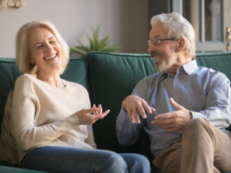 Happy carefree excited elderly family couple laughing, joking, talking, sharing good news, enjoying common weekend time in cozy living room, old people funny activities concept.