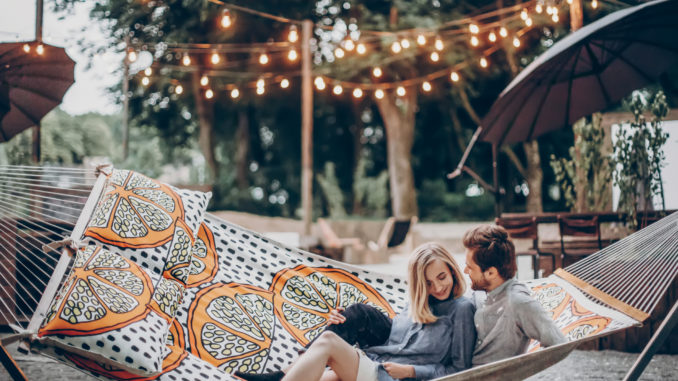 Stylish hipster couple cuddling and relaxing in hammock under retro lights in evening summer park. rustic men and women embracing and resting in forest. space for text. summer vacation