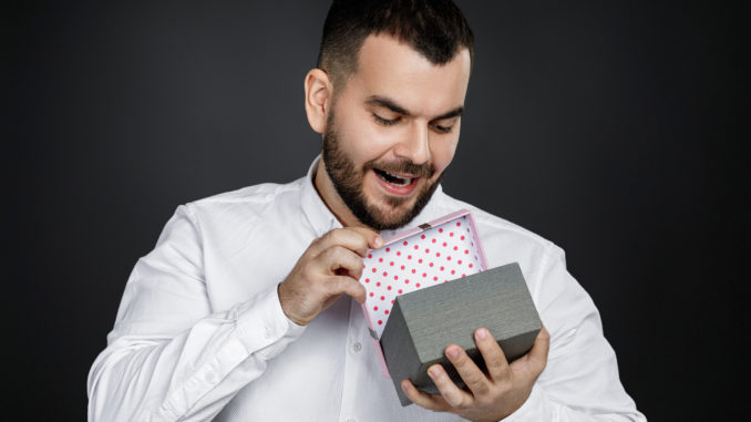 Portrait of handsome bearded man in white shirt opens gift box isolated on black background