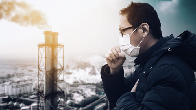 Man wearing mask against smog and air pollution factory background.