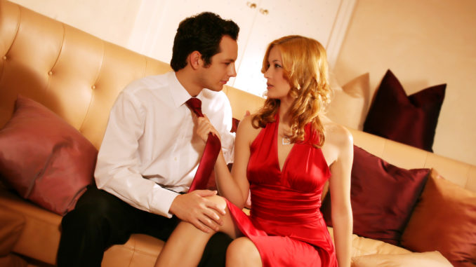 A attractive, young and rich couple is sitting on a lounge and have an argue