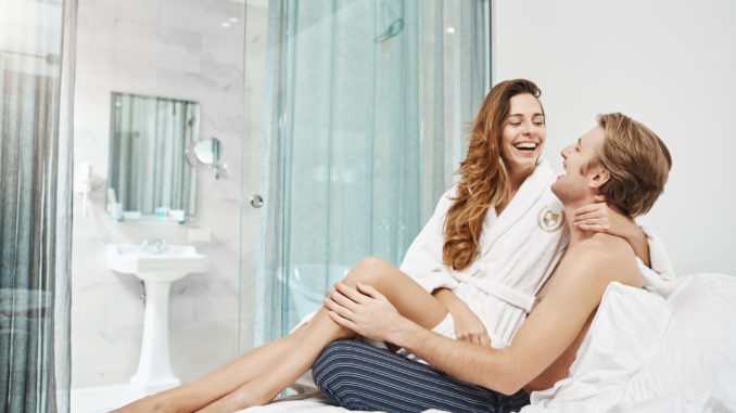 Emotive happy european couple laughing and cuddling while sitting in hotel bedroom in daytime