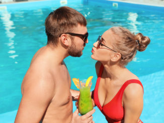 Young couple with refreshing cocktails near swimming pool at resort