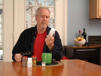 A man of retirement age reading the label of a vitamin bottle