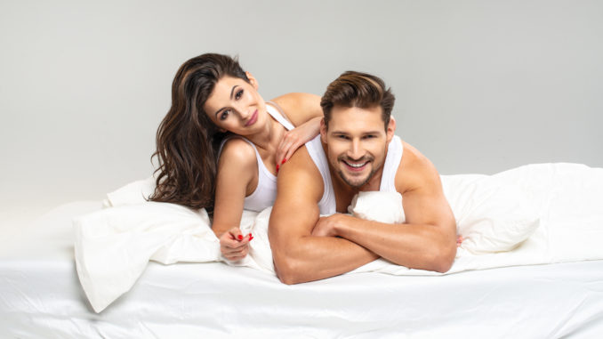 Happy summer couple in white bed
