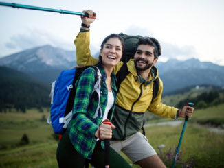 Backpackers happy beautiful couple hiking with sticks