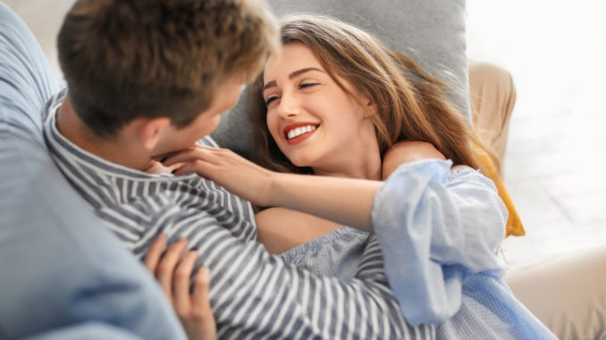 Happy young couple resting on sofa at home