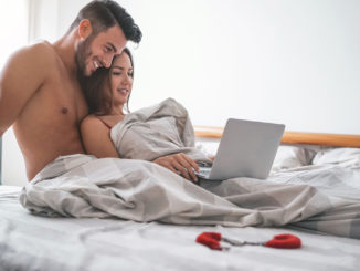 Happy couple watching on computer while lying on bed under blanket