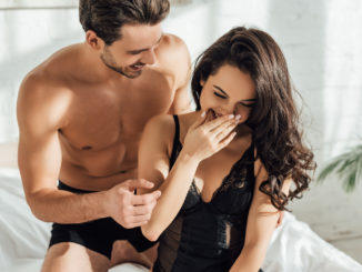 Boyfriend and pretty girlfriend laughing on bed in bedroom