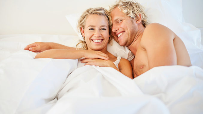 Happy young couple relaxing in bed.