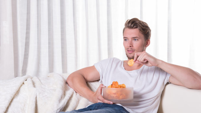 Young man sitting on couch and eating chips.
