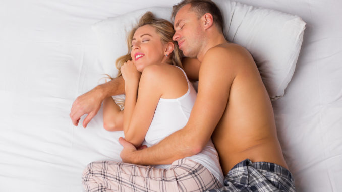 Happy couple sleeping and cuddling in bed