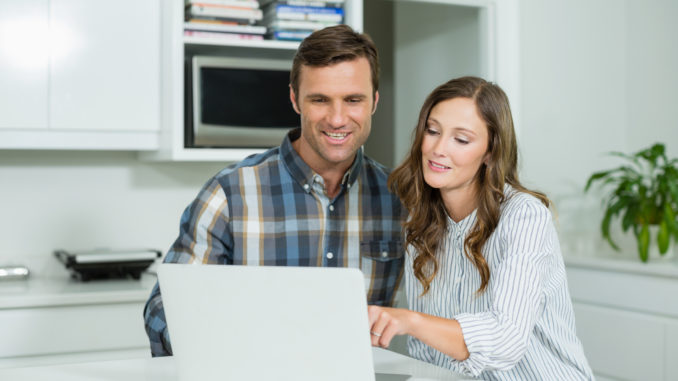 Happy couple interacting with each other while using laptop in living room at home