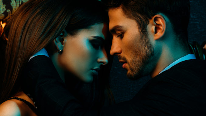 Close-up portrait of a passionate couple in elegant evening dresses.