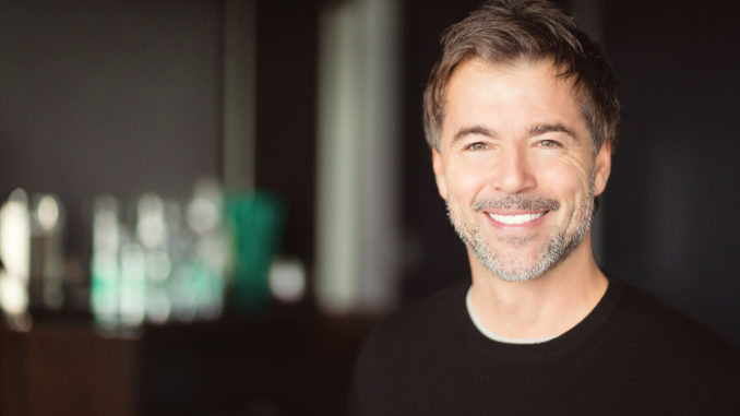 A handsome smiling middle-aged man with a short grey beard and brown hair.