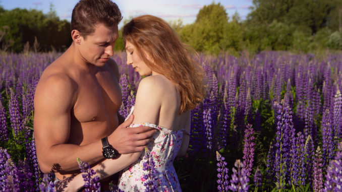 A brutal, pumped-up men undresses his favorite red-haired women on a blooming field on a Sunny day. portrait of a couple in love