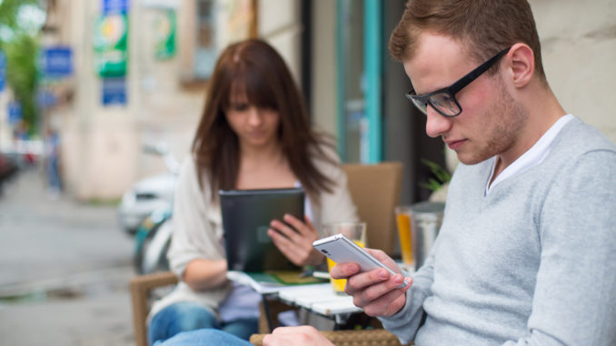Man with cell phone and the women with the iPad sitting in a café. Secluded alley in a background.