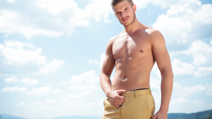 Young topless man posing outdoor with his hand on his pants while looking into the camera