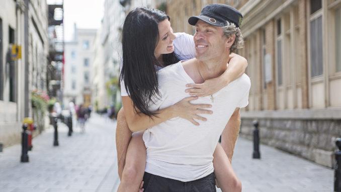 A Man giving piggyback ride to girlfriend, having fun