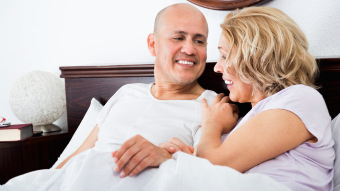 Cheerful mature loving couple lounging in bed after awaking cuddling