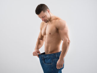 Mid adult muscular man looking at weight loss while holding old jeans against white background
