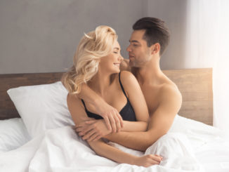 Young couple men and women intimate relationship on bed hugging