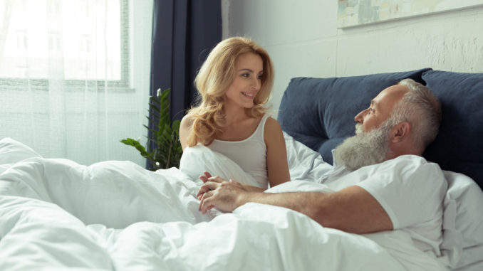 Beautiful happy mature couple lying together in bed and smiling each other