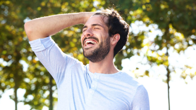 Portrait of happy young man smiling outdoors with hand in hair