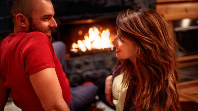 Young couple in love at home front of fireplace