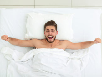 Top view. happy man waking up in a comfortable bed .photo with copy space