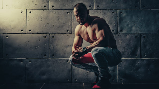 Strong bodybuilder athletic man pumping up muscles workout bodybuilding concept background - muscular bodybuilder handsome man doing exercises in gym naked torso
