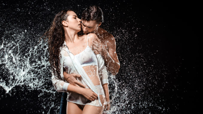 portrait of young couple swilled with water isolated on black